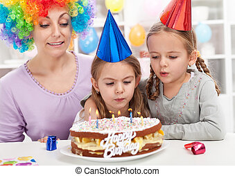 Birthday girl blowing out candles on a cake