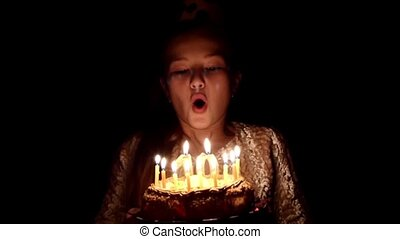 birthday girl blows out candles on a cake, slow motion