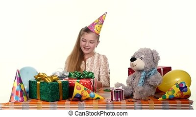 birthday girl looks with admiration at his gifts. around it are soft toys and holiday decorations