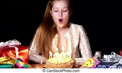 Birthday- girl worries make wish and then blows out the candles on a black background