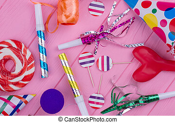 Birthday party accessories on pink wood.