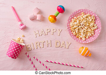 Birthday party background, border of confetti, sweets, lollipops and gift on pink surface, copy space, top view