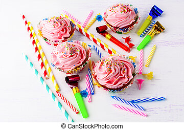 Birthday party concept with decorated pink cupcakes and candles