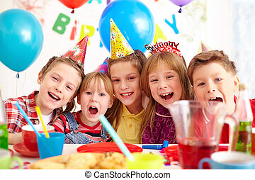 Group of adorable kids looking at camera at birthday party