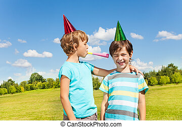 Two boys on birthday party having fun with blowing into noisemaker loudly standing together in the park