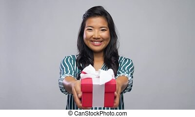 smiling young asian woman holding gift box - birthday ...