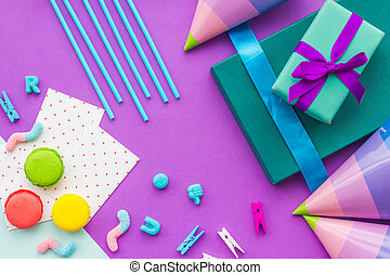 Birthday wrapped gifts and party hats on purple background...