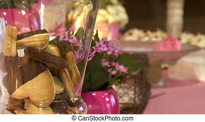 A set with chocolate biscuits, flowers, cake pops and candles. Wedding accessories in a soft, elegant and pink presentation. Decoration for a celebration: a special event, a party or a birthday. Saint Valentine's day stuff. St. Valentine's biscuits. Chocolate cookies with heart shape.