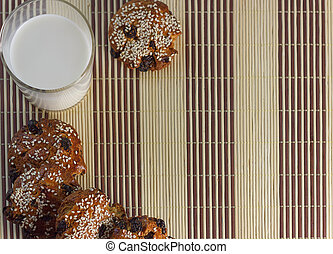 Biscuits on the table with sesame seeds, raisins and a glass of milk