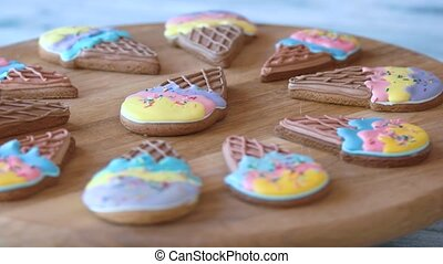Biscuits with colorful glaze on wooden board. Colorful glazed ice cream shaped cookies. Pastry from natural ingredients.