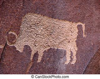 anasazi petroglyph of bison on reddish brown sandstone wall