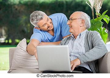 bistå, laptop, sköta, användande, senior, leende herre