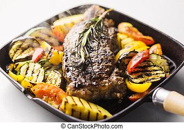 beef steak with grilled vegetables in skillet