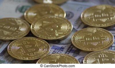 Bit Coin BTC coins rotating on bills of dollars. Virtual...