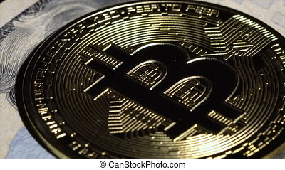Bitcoin coin and 20 dollar bill rotate on the table