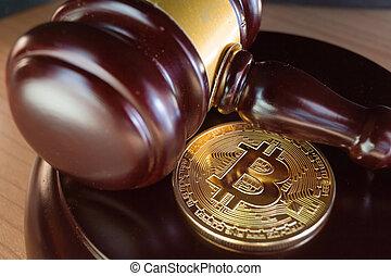 Bitcoin coin and gavel on a desk.