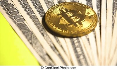 Bitcoin digital currency and dollars at yellow background....