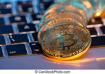 Bitcoin gold coins with laptop keyboard. Virtual cryptocurrency concept.