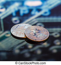 Bitcoin gold, silver and copper coins and defocused printed circuit background. Virtual cryptocurrency concept.