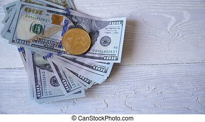 Bitcoin golden coins on a table with dollar banknotes....