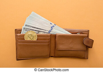Bitcoins, hundred dollar bills and leather wallet