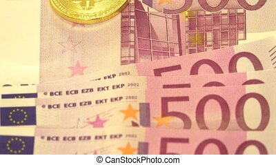 Bitcoin over pile of five hundred euro banknotes