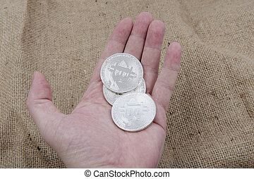 Bitcoins on a hand with wooden background