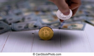 bitcoins with dollar bills on a white table