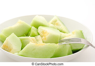 Many bite sized cut melon on the plate with fork
