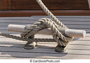Detail of a rope tied-up on wooden bitt securing boat to dock