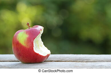 Bitten apple on a woden table in garden with copy sapace
