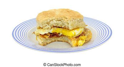 Bitten breakfast sandwich on blue plate