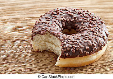 Bitten chocolate donut on a wooden table