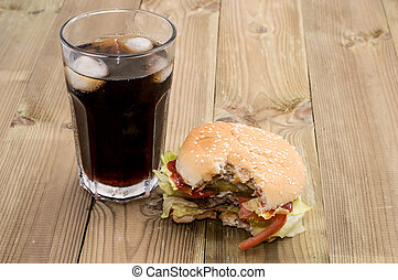 Bitten Off Burger with Softdrink on wooden background