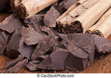 Bitter chocolate in pieces on a brown background with...
