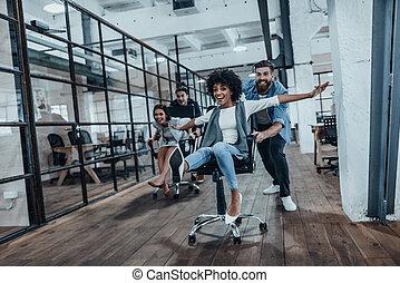biuro, fun., cztery, młody, radosny, handlowy zaludniają, w, przemądrzały przypadkowy, nosić, mająca zabawa, znowu, biegi, na, biurowe krzesła, i, uśmiechanie się