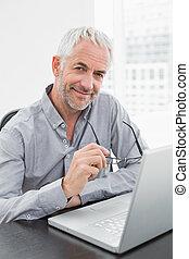 biuro, laptop, dojrzały, biznesmen, używając, uśmiechanie się