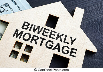 Biweekly mortgage. Wooden model of house and money.