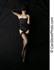 Bizarre shoot of sexy lady in lingerie over black silk backgroun