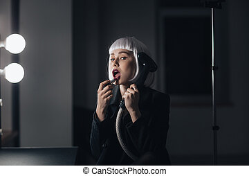 Bizarre woman holding steamer and applying lipstick in dressing room