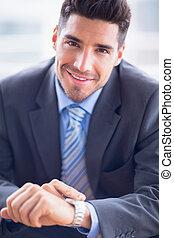 biznesmen, posiedzenie, kontrola, jego, pilnowanie, uśmiechanie się, na aparacie fotograficzny