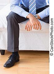 biznesmen, posiedzenie, na, jego, łóżko