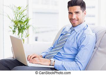 biznesmen, posiedzenie na nachylają, używając, jego, laptop, uśmiechanie się, na aparacie fotograficzny