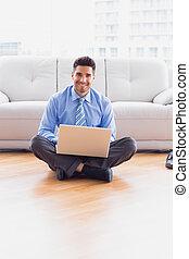 biznesmen, posiedzenie na podłodze, używając, jego, laptop, uśmiechanie się, na aparacie fotograficzny
