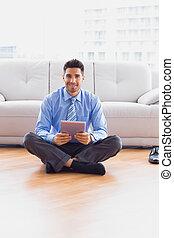 biznesmen, posiedzenie na podłodze, używając, tabliczka, uśmiechanie się, na aparacie fotograficzny