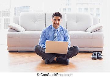 biznesmen, posiedzenie na podłodze, używający laptop, uśmiechanie się, na aparacie fotograficzny