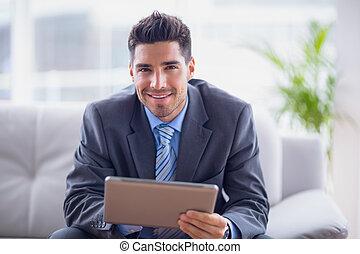 biznesmen, posiedzenie na sofie, używając, jego, tabliczka, uśmiechanie się, na aparacie fotograficzny