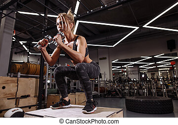 BJ. gorgeouse beautiful woman doing exercise on the box in the gym. cross fit