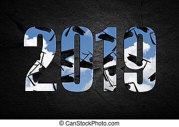 black 2019 graduation caps in sky