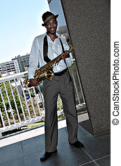 Black African Amercian Man Outdoors With a Saxophone In...